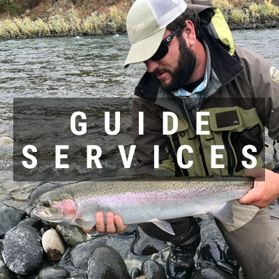 Angler holding a steelhead Guide Services button